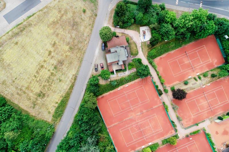Vista aerea verticale di un campo da tennis accanto ad una casa e di una via con le automobili parcheggiate vicino ad un prato in fotografia stock