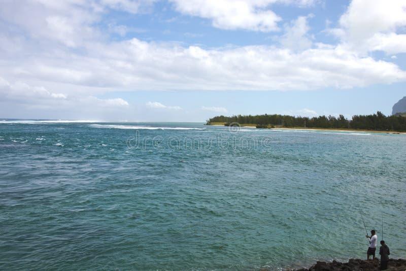 Vista agradável do oceano ndian da praia da ilha de Maurícias Céu bonito, ponto baixo azul nebuloso e dois pescadores no fotos de stock