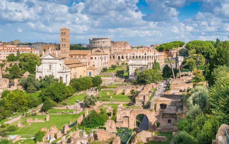 Vista agradável em Roman Forum, com a basílica de Santa Francesca Romana, de Colosseum e de Titus Arch Indicadores velhos bonitos fotografia de stock royalty free