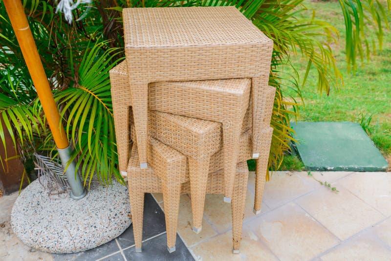 Vista agradable de las sillas o de las tablas tejidas patio apiladas en jardín tropical imagenes de archivo