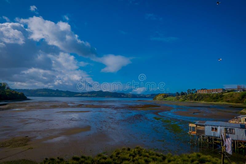 Vista al aire libre de casas de madera coorful hermosas en palafitos de los zancos, en una opinión del día de la marea baja en dí fotos de archivo