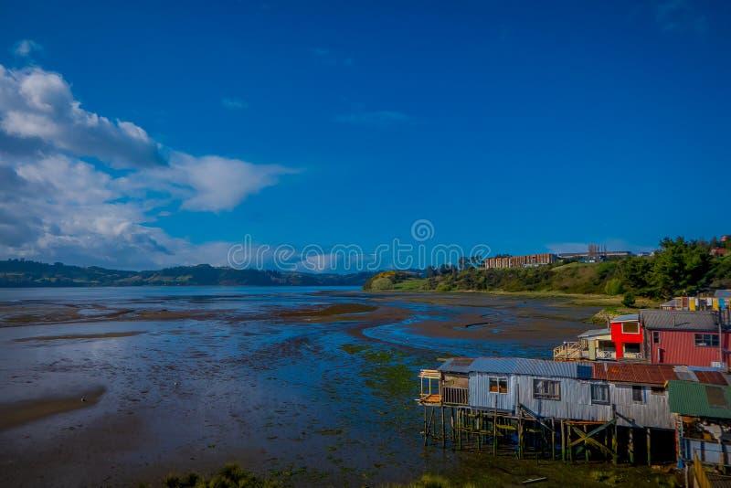 Vista al aire libre de casas de madera coorful hermosas en palafitos de los zancos, en una opinión del día de la marea baja en dí imagenes de archivo