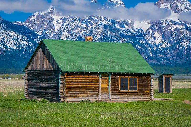 Vista al aire libre de la cabina de madera con el tejado verde en una pradera de oro de la hierba contra las montañas magníficas  foto de archivo