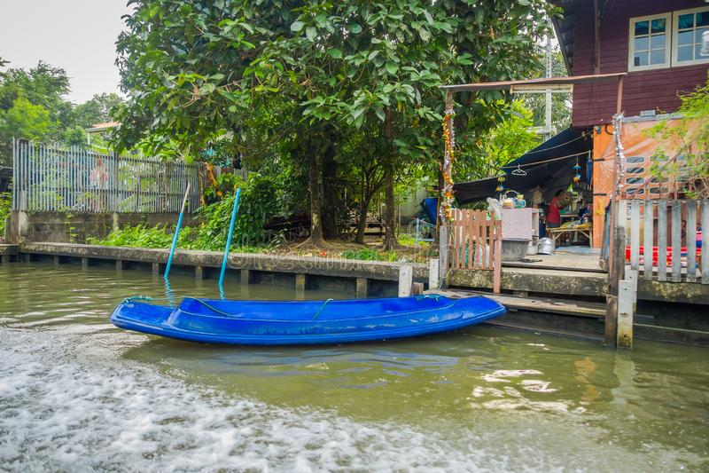 Vista al aire libre del bote pequeño plástico azul en la orilla en el canal o la explosión Luang de yai de Khlong en Tailandia fotografía de archivo