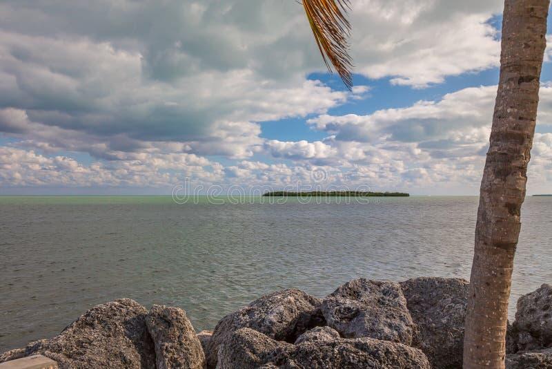 Vista al mar con las palmeras y rocas y nubes hermosas imagen de archivo