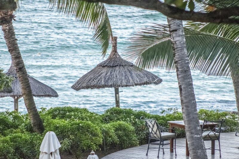 Vista al mar sobre decking con la tabla y sillas con los paraguas de la paja fotografía de archivo