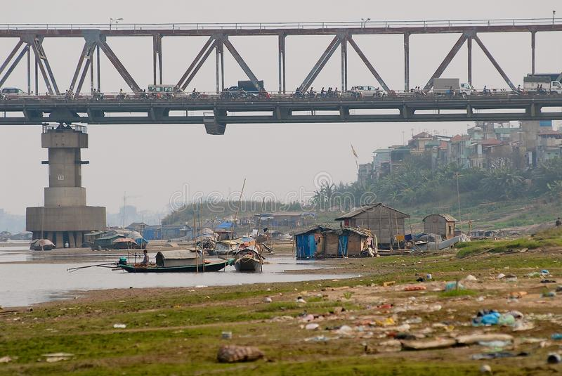 Vista al puente con tráfico intensivo y área residencial pobre debajo y basura en el banco del río en Hanoi, Vietnam imagen de archivo libre de regalías