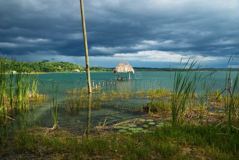 Vista al villaggio con il bacino lungo la riva con gli uccelli, EL Remate, Peten, Guatemala del lago immagini stock