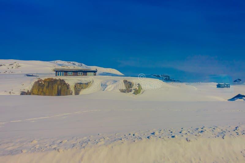 Vista all'aperto di alcune case di legno quasi coperte di neve durante il wsnowstorm pesante, a Gol Mountain Area immagine stock