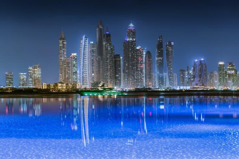 Vista all'orizzonte illuminato del porticciolo del Dubai alla notte immagini stock