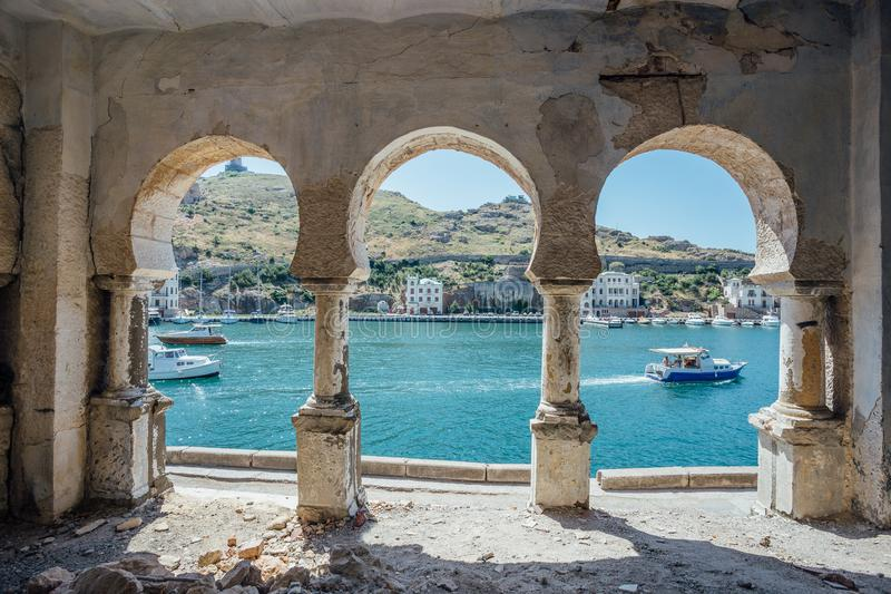 Vista alla baia di Balaklava attraverso il balcone incurvato nello stile orientale Palazzo abbandonato sulla costa di Mar Nero fotografia stock