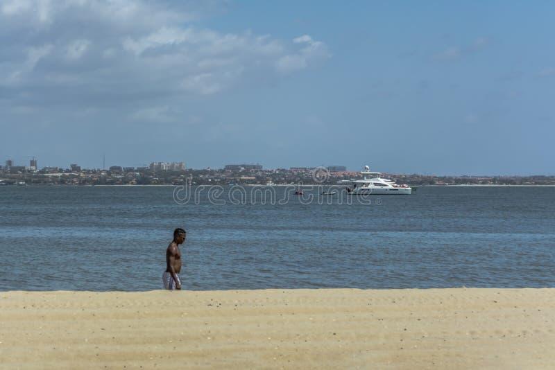 Vista alla spiaggia sull'isola di Mussulo, con la camminata di un uomo, acqua con una barca ed i getti, sulla città di Luanda e s fotografia stock