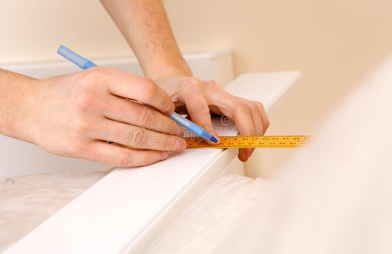 Vista alta vicina del righello e della matita di tenuta laboriosi mentre facendo i segni sul legno alla tavola fotografia stock