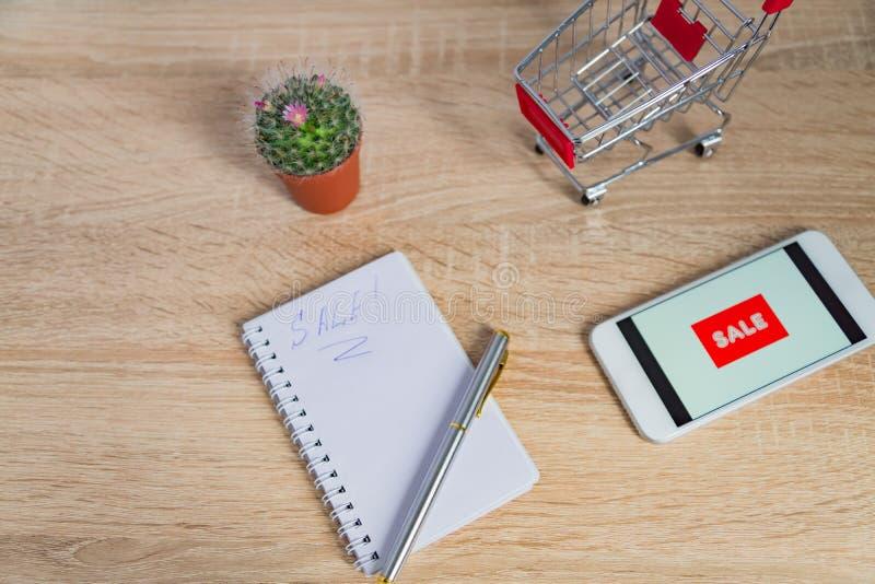 Vista alta vicina della scrivania con lo smartphone bianco con il testo di vendita, la nota ed il piccolo carrello Affare di tecn fotografia stock