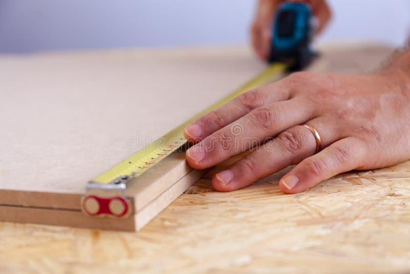 Vista alta vicina delle mani di un uomo che misurano un pezzo di legno con nastro adesivo handyman misura immagini stock libere da diritti