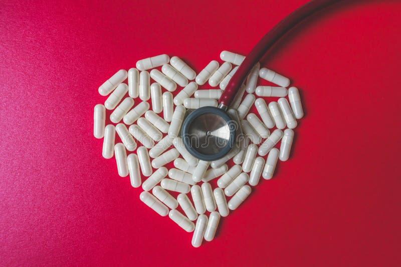 Vista alta vicina di uno stetoscopio rosso e delle capsule bianche che formano una forma del cuore su fondo rosso con lo spazio d fotografie stock libere da diritti