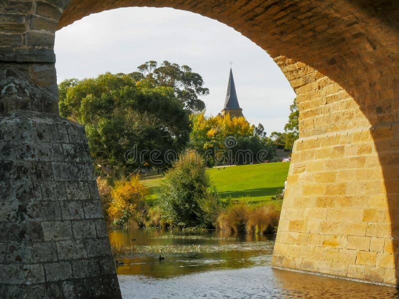 Vista alta vicina di vecchio ponte di pietra storico e della guglia della chiesa cattolica di St John immagini stock