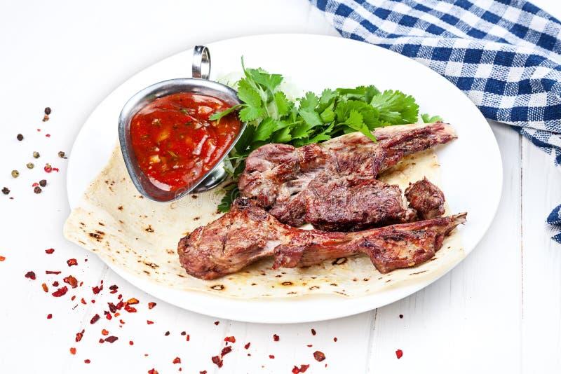 Vista alta vicina sul servito su cucinato sull'agnello della griglia sull'osso carne del barbecue o dello shashlik sulla pita Keb immagini stock