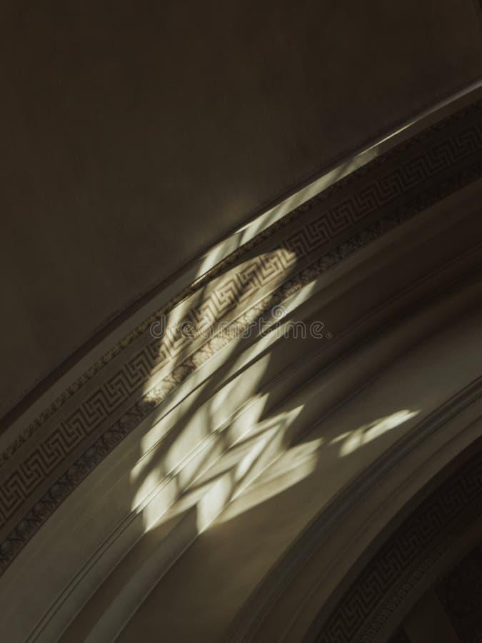 Vista angolo basso di un soffitto con decorazioni incisive e luce solare immagini stock libere da diritti