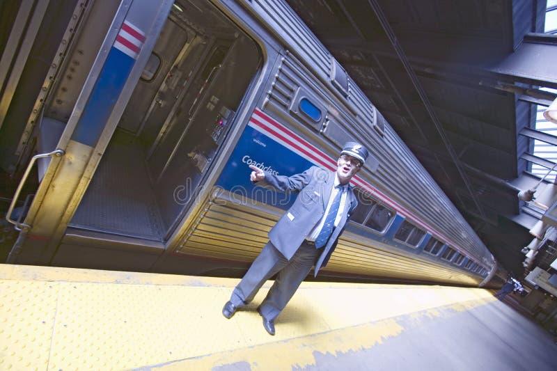 A vista angular do condutor na plataforma do trem de Amtrak anuncia tudo a bordo no estação de caminhos-de-ferro da costa leste n imagem de stock royalty free