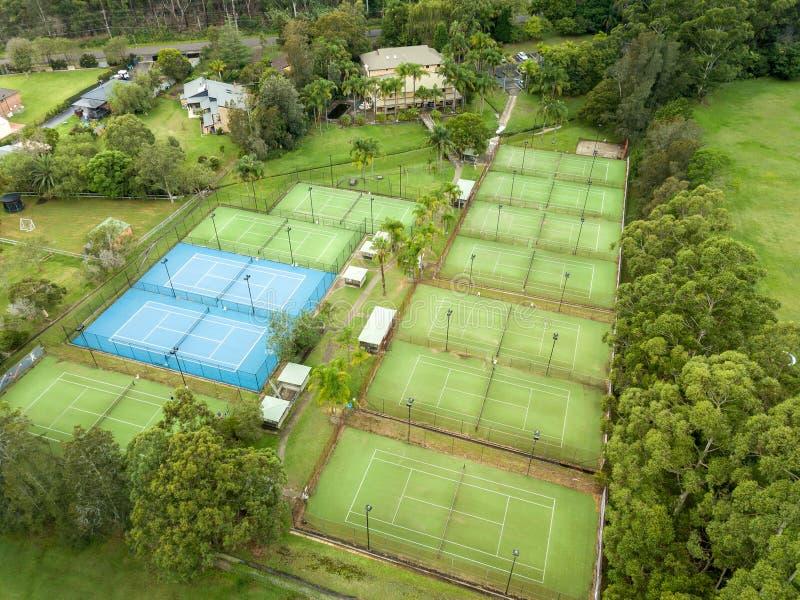 Vista angulosa aérea del centro y de la instalación del tenis con las cortes duras azules y las cortes de hierba artificiales ver fotos de archivo