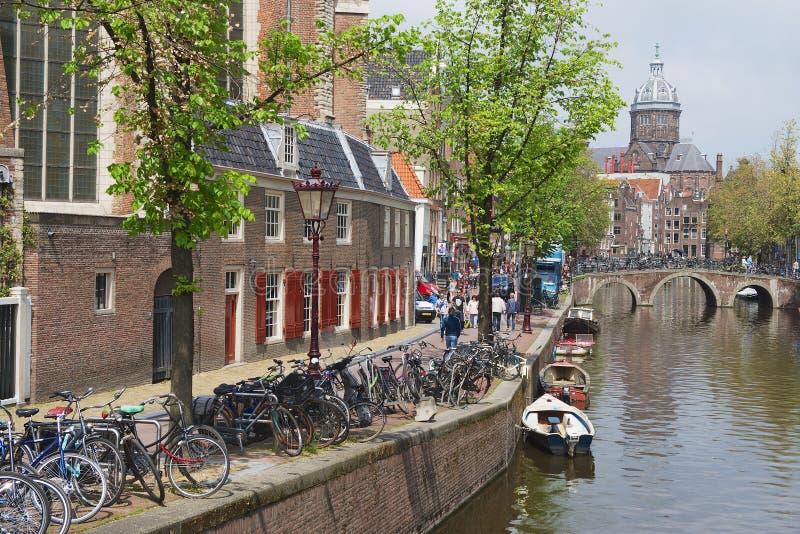 Vista ao canal com as bicicletas estacionadas e a basílica da São Nicolau no fundo em Amsterdão, Países Baixos imagem de stock