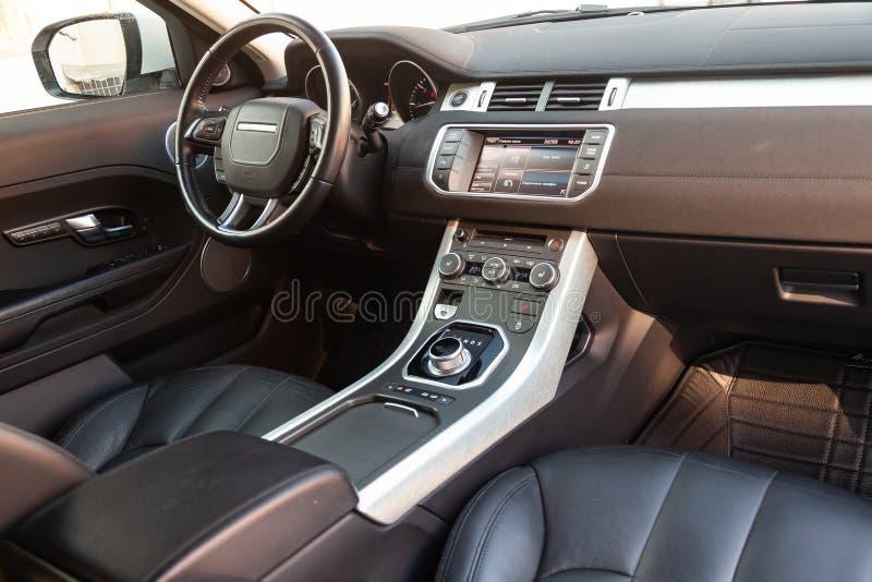 Vista ao interior da terra Rover Evoque com painel, pulso de disparo, sistema de meios, assentos e shiftgear dianteiros ap?s a li imagens de stock royalty free