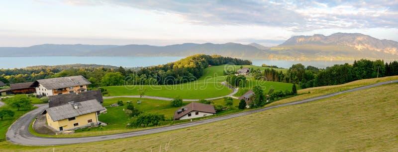 Vista ao lago Attersee com os prados verdes do pasto e cordilheira dos cumes perto de Nussdorf Salzburg, Áustria fotografia de stock royalty free
