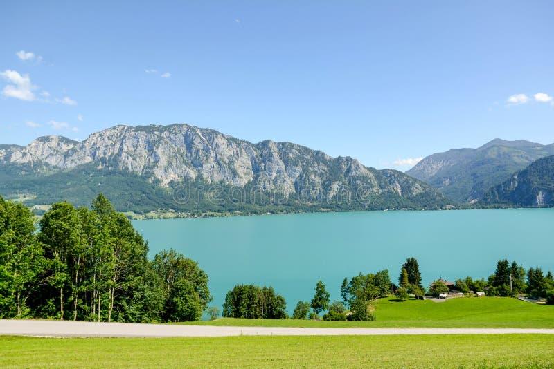Vista ao lago Attersee com os prados verdes do pasto e cordilheira dos cumes perto de Nussdorf Salzburg, Áustria imagem de stock