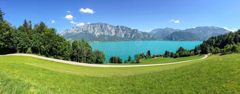 Vista ao lago Attersee com os prados verdes do pasto e cordilheira dos cumes perto de Nussdorf Salzburg, Áustria imagens de stock royalty free