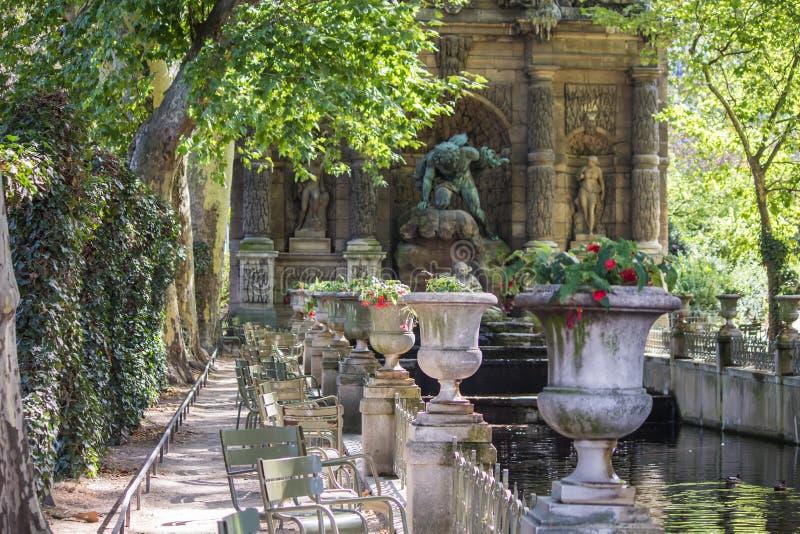 Vista ao longo da fileira das urnas de pedra a Fontaine de Medici, Jardin de Luxemburgo, Paris imagem de stock