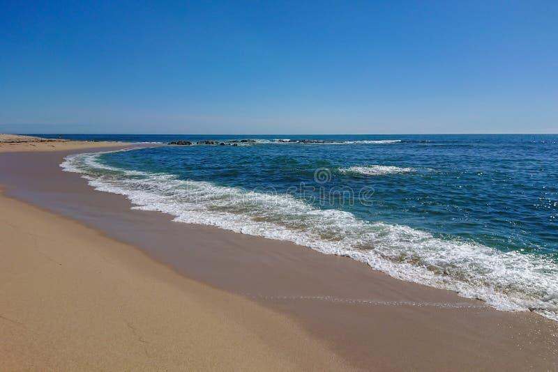 Vista ao longo da linha costeira de Sandy Beach vazio em Portugal em um dia de verão ensolarado com céu azul, foto de stock