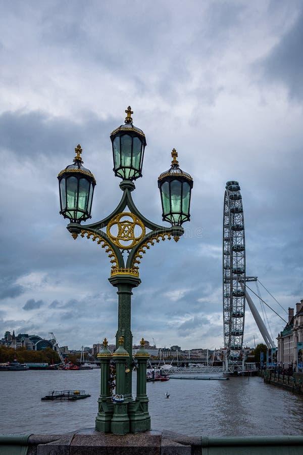 Vista aperta vicina di vecchia lampada di via variopinta con l'occhio di Londra nei precedenti fotografia stock