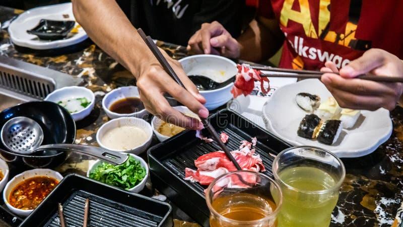 Vista aproximada de chopstick segurando uma fatia de carne crua antes de mergulhar na sopa em ebulição imagens de stock