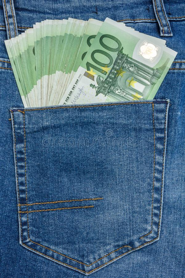Vista ascendente cercana a 100 billetes de banco del euro que se pegan hacia fuera de un bolsillo de los tejanos fotografía de archivo libre de regalías