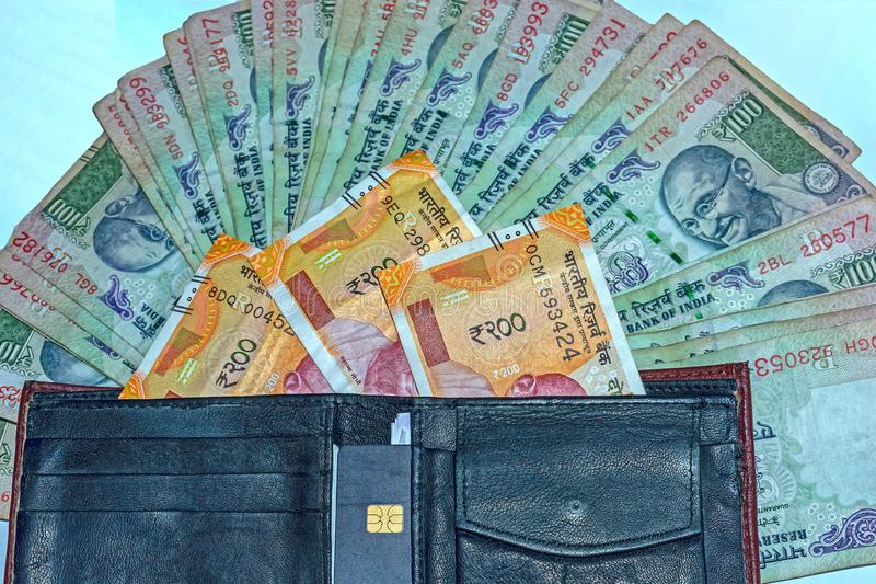 Vista ascendente cercana de la cartera con 200 rupias y viejas 100 rupias de billetes de banco indios en fondo fotografía de archivo libre de regalías