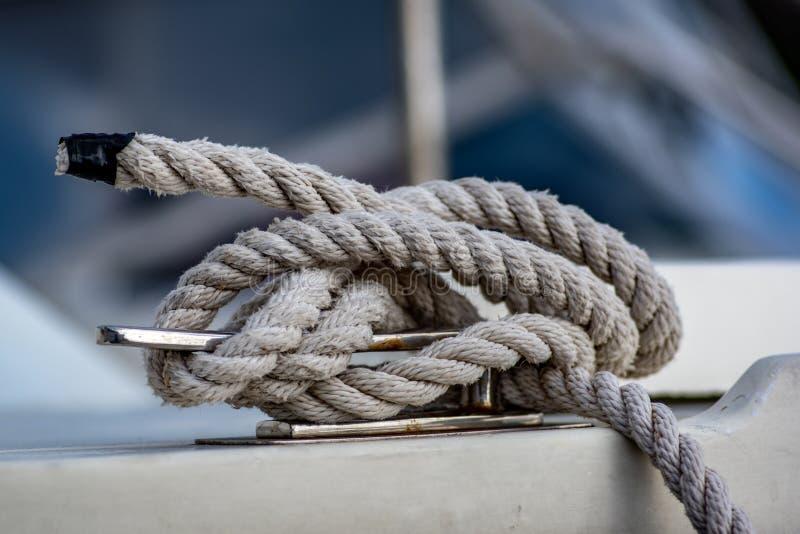 Vista ascendente cercana de la cuerda blanca atada alrededor del bolardo de la nave imagen de archivo libre de regalías