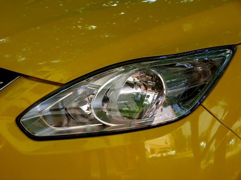 vista ascendente cercana de la lente color plata de la linterna detalle moderno brillante amarillo del coche foto de archivo