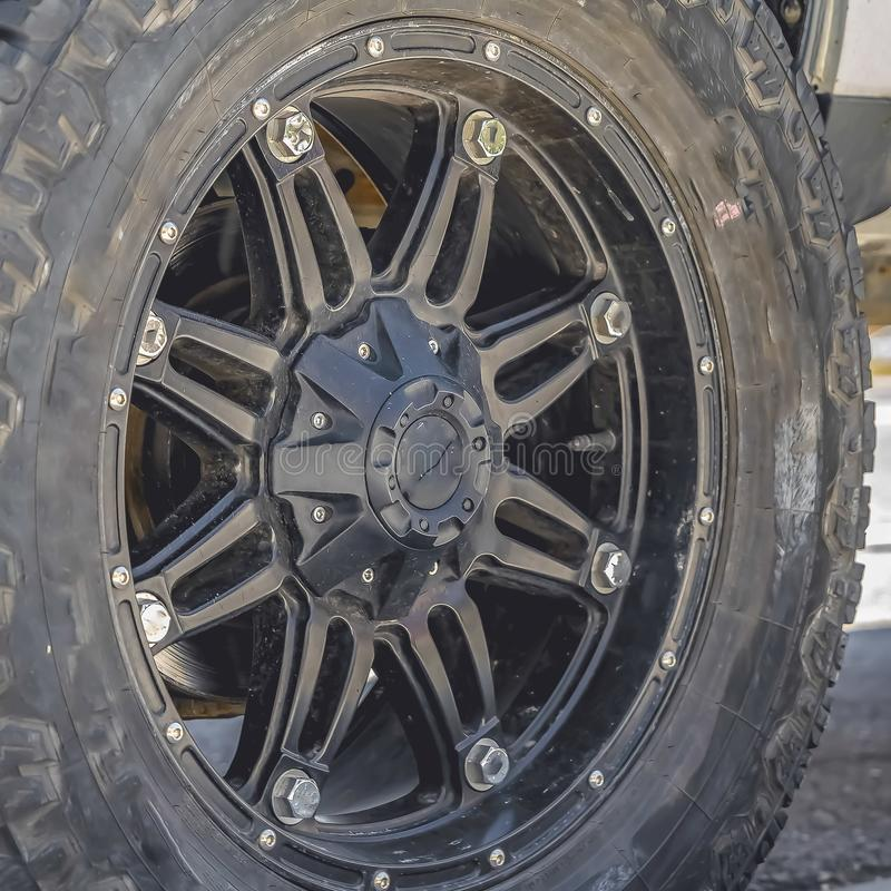 Vista ascendente cercana de la rueda de goma negra de un vehículo parqueado en un camino iluminado por el sol fotos de archivo
