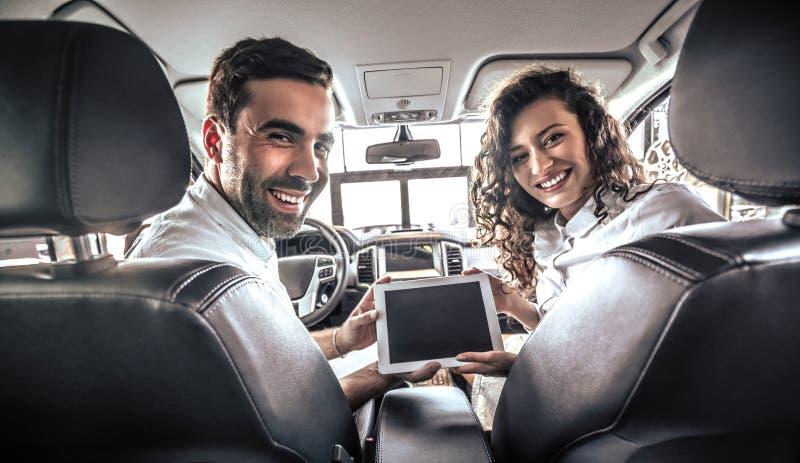 Vista ascendente cercana de los pares que se sientan en un nuevo coche con el ordenador de la PC de la tableta en el salón del au fotografía de archivo libre de regalías