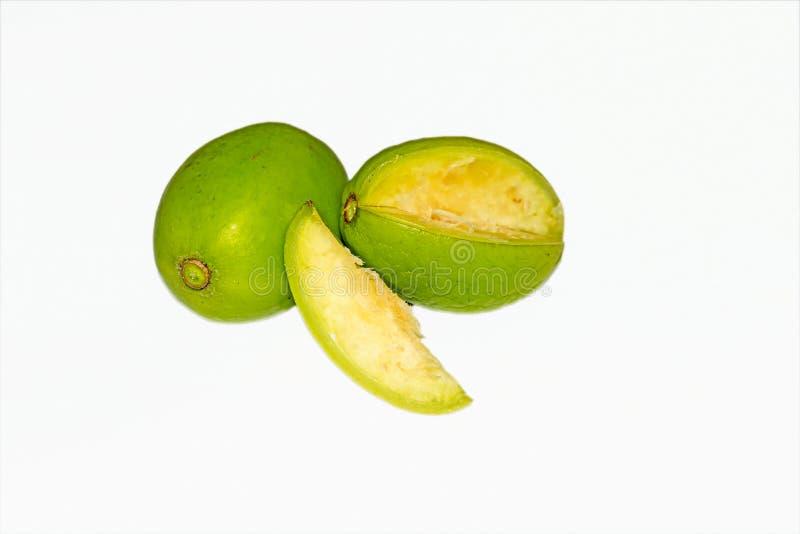 Vista ascendente cercana de los pedazos cortados de frutas verdes frescas de los dulcis del Spondias en el fondo blanco foto de archivo libre de regalías