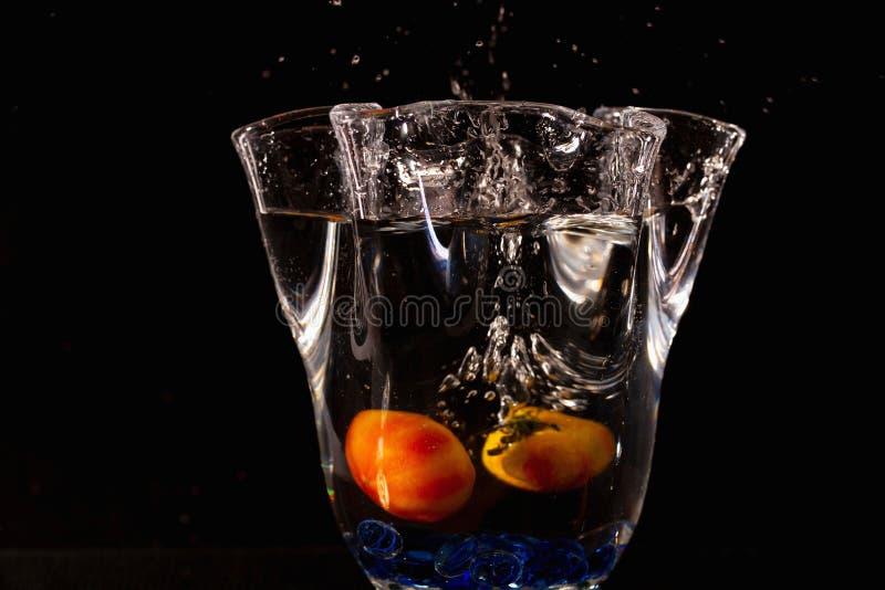 Vista ascendente cercana del florero con salpicar el agua y las frutas amarillas en ella en fondo negro foto de archivo libre de regalías