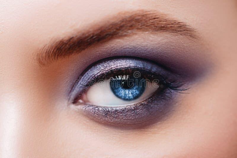 Vista ascendente cercana del ojo azul de la mujer con los tonos hermosos y el maquillaje negro del l?piz de ojos foto de archivo