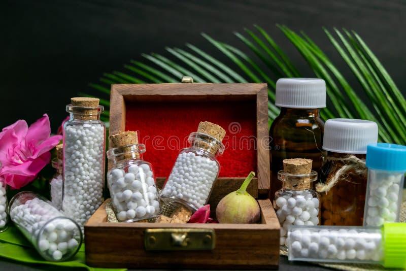 Vista ascendente cercana del vidrio homeopático y de las botellas plásticas de la medicina en caja vieja de madera con el brote d imagenes de archivo