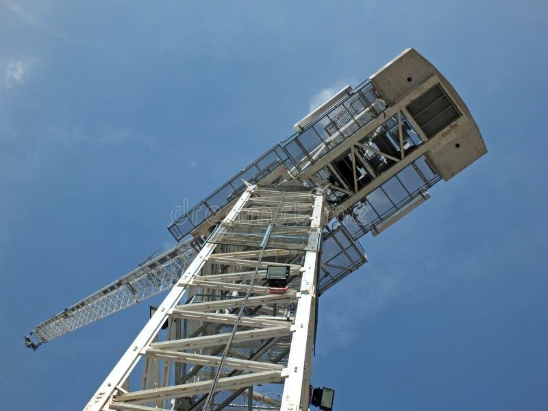 Vista ascendente de una grúa de construcción blanca grande de la torre contra un cielo azul imagenes de archivo