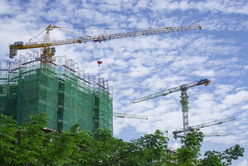 Vista ascendente del edificio prefabricado y de la máquina móvil alta grande de grúa en la construcción, cubierta del andamio por imagenes de archivo