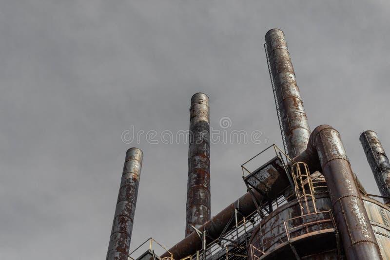 Vista ascendente extrema das chaminés em alto-fornos em uma fresa de aço industrial, céu cinzento imagem de stock royalty free