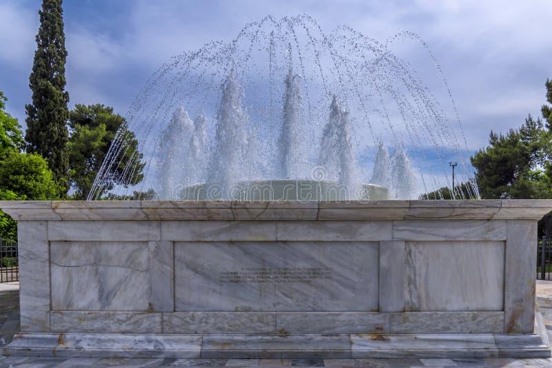Vista ascendente próxima da água de jorro da fonte de mármore na frente da construção neo-clássica de Zappeion Salão na paridade  fotografia de stock