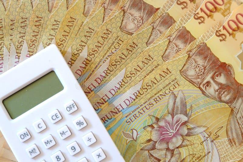 Vista ascendente próxima da cédula de Brunei Darussalam Darussalam Dinheiro com calculadora Dólar fotografia de stock