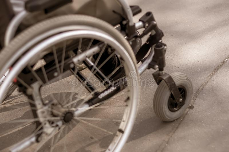 Vista ascendente próxima da cadeira de rodas com a pessoa exterior foto de stock